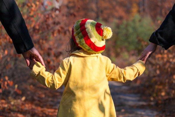 Родители держат девочку за руку