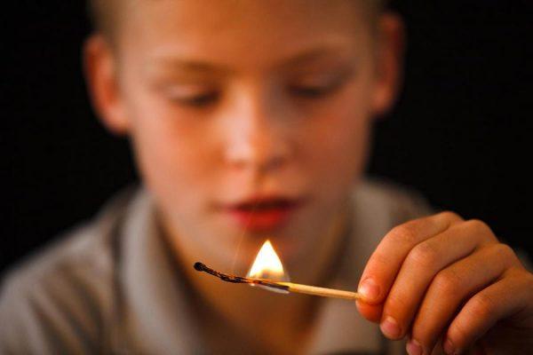 Мальчик смотрит на зажжённую спичку