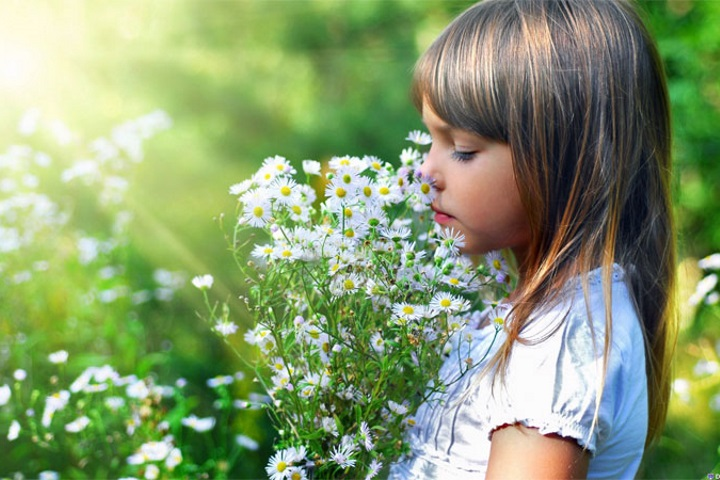 Girl sniffing a flower