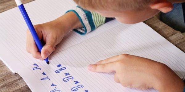 Мальчик выводит буквы