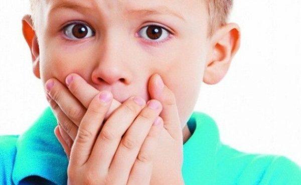 Мальчик прикрыл рот руками
