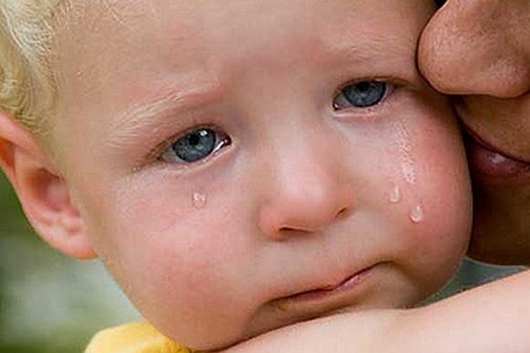 Плачущего ребенка успокаивает взрослый