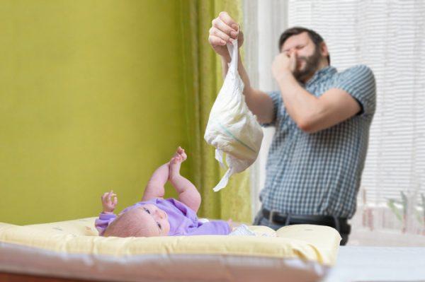 Папа меняет малышу подгузник