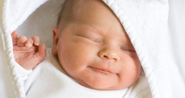 Новорожденный улыбается
