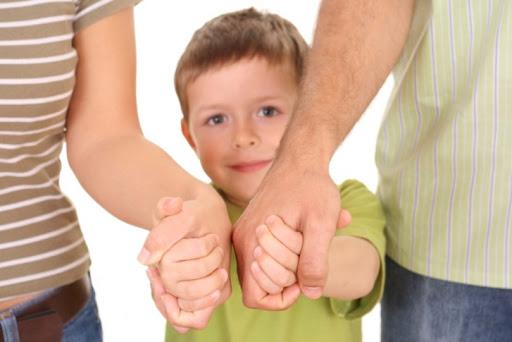 Мальчик держит маму и папу за руку