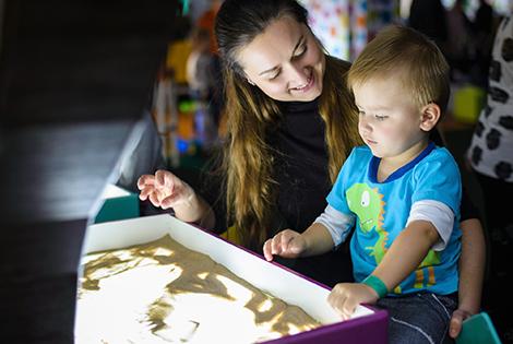 Мама с ребенком рисуют в песочнице