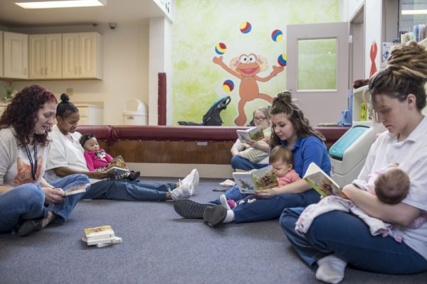 Слева, социальный работник Сью Уриш и заключенная Латонья Джексон и ее 5-месячная дочь Оливия Уолтон; Мишель Нивилл, со своим 3-месячным сыном Далтоном Нивиллом; Дестини Дауд с 10-месячной дочерью, Джейлинн Парселл; и Кристин Дакуиц, читающая своей двухмесячной дочери Изабель Манскер