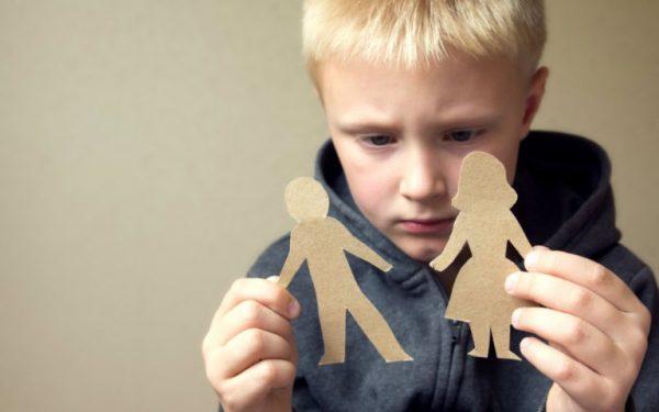 Мальчик держит фигурки из бумаги