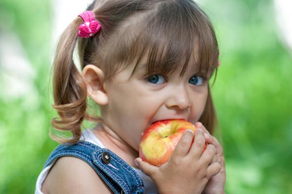 Ребенок ест яблоко. Фото depositphotos