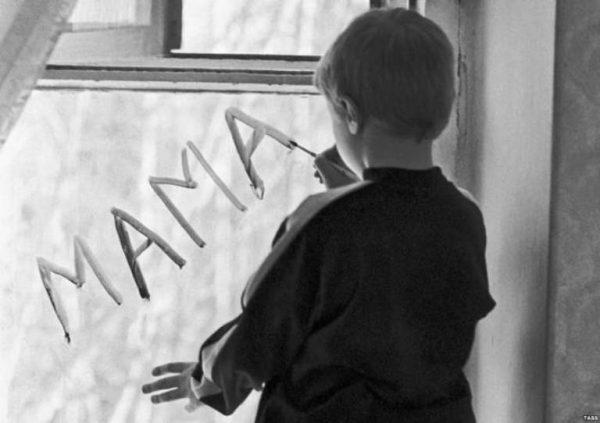 Мальчик пишет на стекле мама