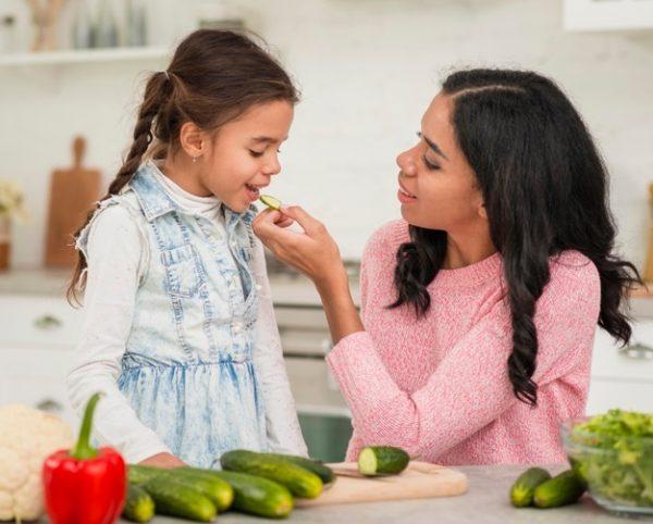 Freepik Мама кормит дочку овощами