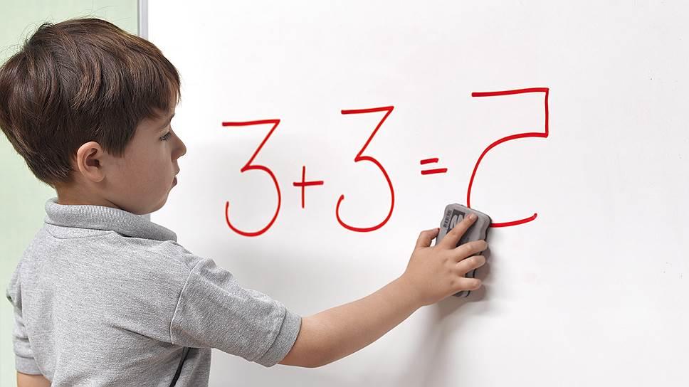 The boy writes on the blackboard