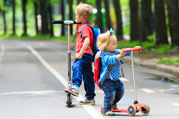 children ride scooters
