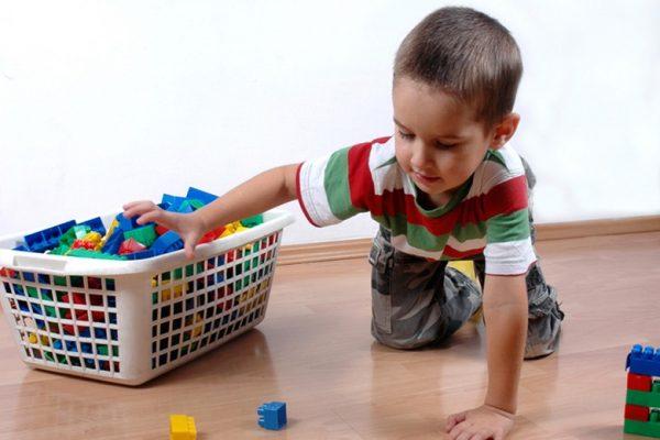 ребенок собирает игрушки